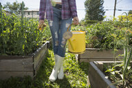 Young woman wellingtons holding watering can garden - HEROF28429