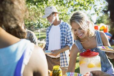 Smiling neighbors at potluck table - HEROF28435