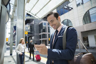Smiling businessman checking cell phone at train station - HEROF28453