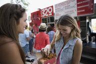 Women eating fries outside food truck - HEROF28480
