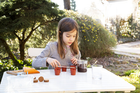 Portrait of little girl at garden table sowing seeds - LVF07855