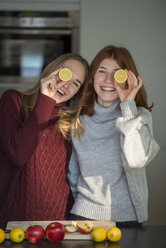 Two laughing friends holding lemon halves in front of their eyes - LBF02415