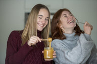 Two best friends tasting honey - LBF02418