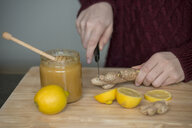 Hands of young woman cutting ginger root on wooden board - LBF02421