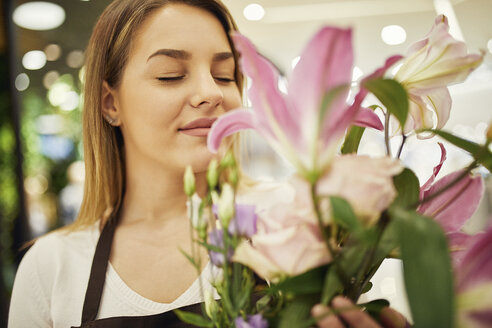 Florist smelling at flower in flower shop - ZEDF01979