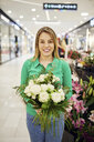 Portrait of smiling florist holding bunch of flowers in flower shop - ZEDF01985