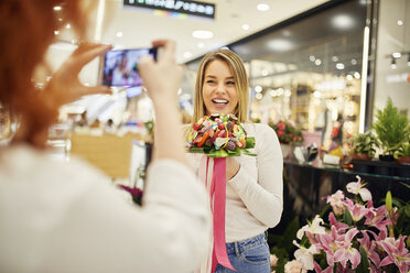 Happy woman holding candy bouquet in a shop posing for a photo - ZEDF01994