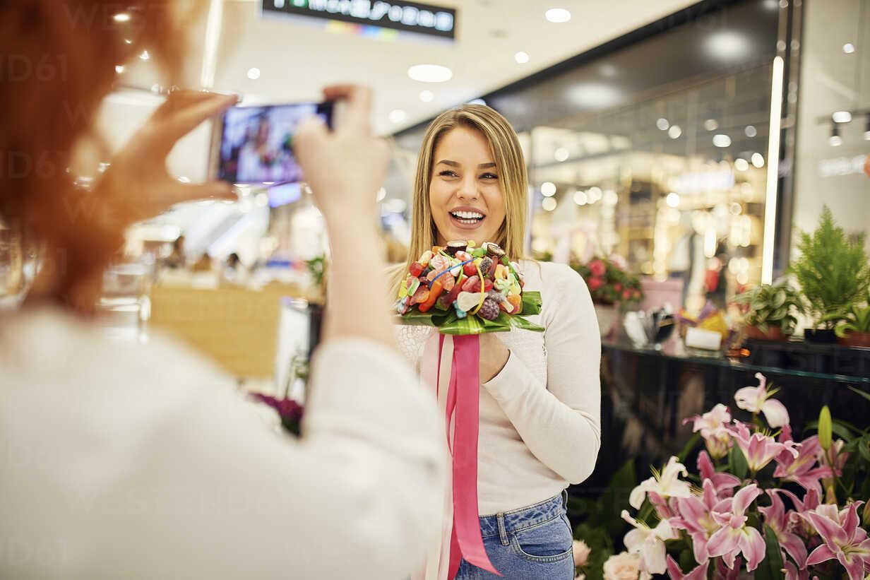 Happy woman holding candy bouquet in a shop posing for a photo - ZEDF01994 - Zeljko Dangubic/Westend61