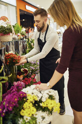 Florist advising customer in flower shop - ZEDF02006