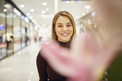 Portrait of smiling woman behind blossom in a shopping arcade - ZEDF02012