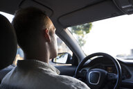 Rear view of young man driving car at sunset - ABZF02245