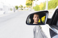 Reflection of young man in wing mirror of a car - ABZF02248