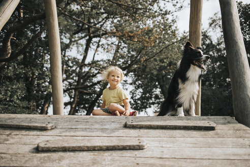 Netherlands, Schiermonnikoog, girl with Border Collie sitting on boardwalk in the forest - DWF00334