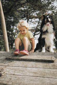 Netherlands, Schiermonnikoog, girl with Border Collie sitting on boardwalk in the forest - DWF00337