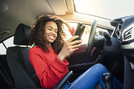 Happy young woman using cell phone in a car - JSMF00805