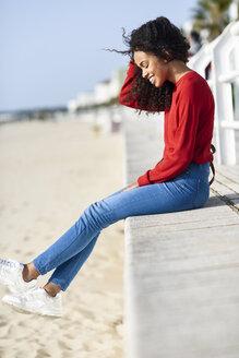 Happy young woman sitting on beach promenade - JSMF00808