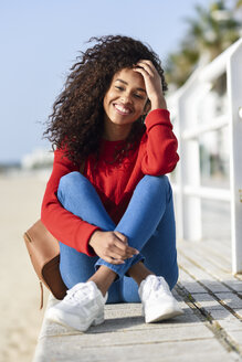 Portrait of happy young woman sitting on beach promenade - JSMF00811