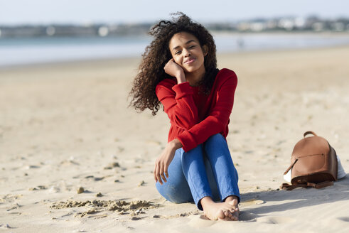 Spain, Andalusia, Puerto de Santa María, Happy young black woman with curly hair enjoying the beach sitting on the sand. Lifestyle and travel concepts. - JSMF00814
