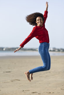 Carefree young woman jumping on the beach - JSMF00823
