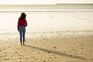 Rear view of young woman standing on the beach at sunset - JSMF00826