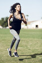 Sporty young woman with earphones running - JSMF00838