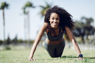 Happy sporty young woman doing push-ups on lawn - JSMF00847