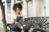 Young woman sitting on a bench using tablet - JSMF00853