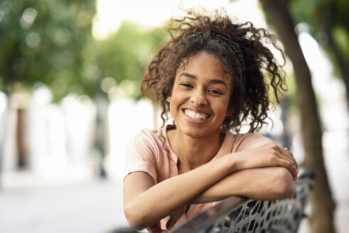 Portrait of happy young woman sitting on a bench - JSMF00856