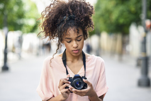 Spain, Andalusia, Jerez de la Frontera, Young black woman with curly hair using reflex SLR camera in urban background. Lifestyle concept. - JSMF00862