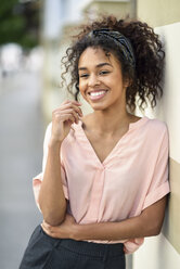 Smiling young woman leaning against a wall looking around - JSMF00868