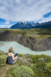 Chile, Patagonia, woman using tablet at a river bend in Torres del Paine National Park - RUNF01479