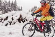 Man riding mountainbike on path in winter forest - SEBF00043