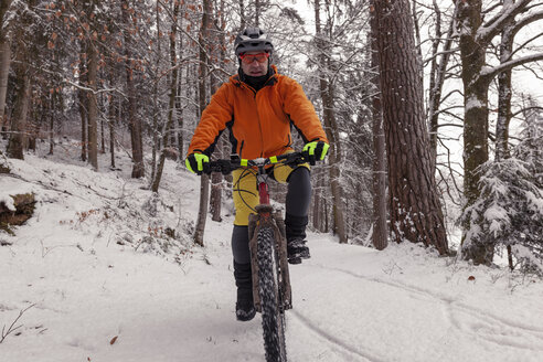 Man riding mountainbike on path in winter forest - SEBF00046