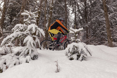 Man riding mountainbike on path in winter forest - SEBF00052