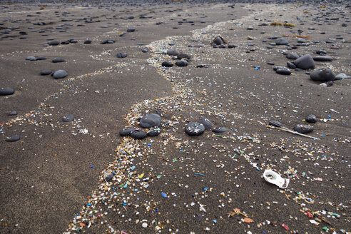 Spain, Canary Islands, Lanzarote, Playa Famara, microplastics, washed up on dark lava sand - SIEF08424
