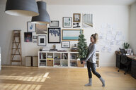 Young woman carrying small Christmas tree in studio - HEROF28488