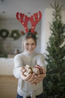 Portrait teenage girl in reindeer antlers holding small Christmas gifts - HEROF28512