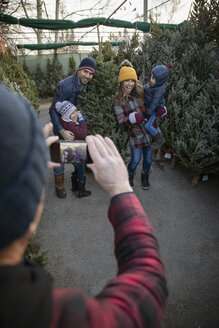 Worker with camera phone photographing happy family shopping for Christmas tree at Christmas market - HEROF28545