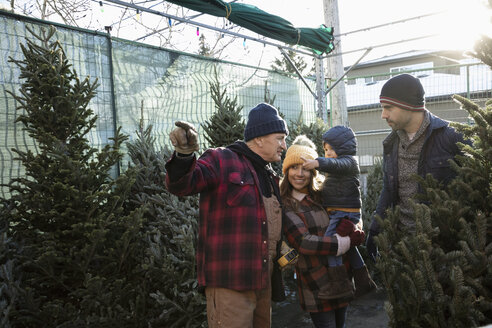 Worker helping family shopping for Christmas tree at Christmas market - HEROF28569