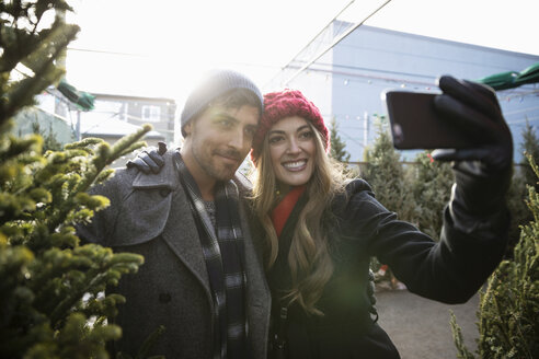 Happy couple taking selfie with Christmas tree at Christmas market - HEROF28590