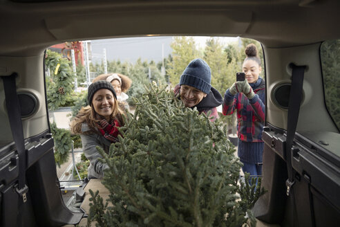 Worker helping family load Christmas tree into SUV at Christmas market - HEROF28596