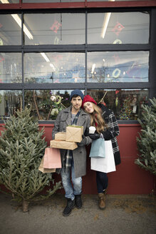 Portrait happy couple shopping for gifts and Christmas tree at Christmas market - HEROF28611