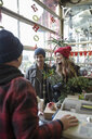 Couple paying for Christmas decorations at Christmas market - HEROF28614