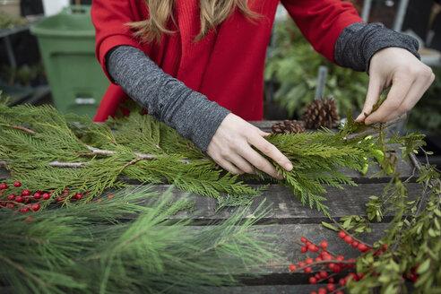 Woman making Christmas swag - HEROF28617