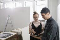 Art gallery owners using digital tablet - HEROF28653