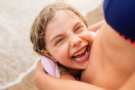 Laughing girl being hugged by mother on beach, Portoferraio, Tuscany, Italy - CUF49771