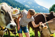 Woman bonding with herd of cows on field, Sonthofen, Bayern, Germany - CUF49867