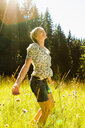 Woman dancing amongst wild flowers in forest, Sonthofen, Bayern, Germany - CUF49885