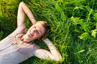 Woman lying down on grass in countryside - CUF49900