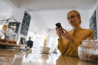 Blond businesswoman using smartphone in a coffee shop, reading text messages - JOSF03144